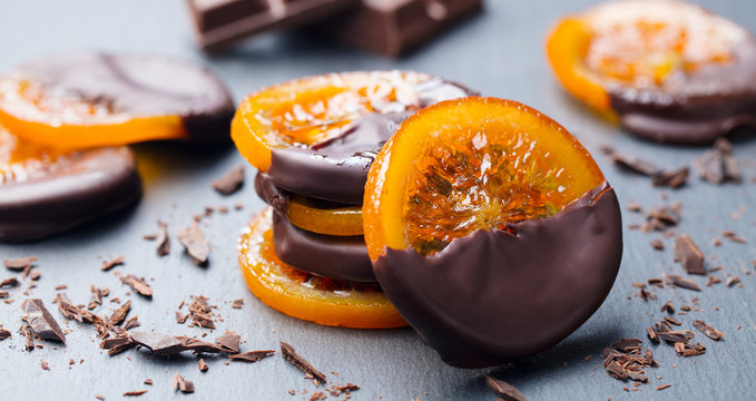 Candied orange slices in chocolate. Slate background. Close up.