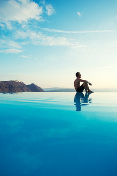 Solitary man sitting on the edge of an infinity pool looking out over the scenic Mediterranean view of the Santorini caldera, Greece