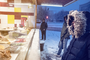 a caucasian girl or woman in a winter jacket with a hood, chooses a street food at a stall in a winter evening city.