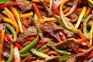 Beef Steak Fajitas with mix pepper, onion and avocado on wooden board