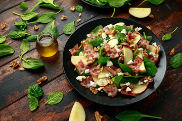 Bacon, Apple Salad with spinach, walnuts and feta cheese. on wooden table. healthy food.