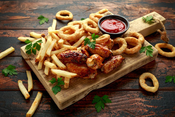 Fried Chicken wings with onion rings, french fries and dipping sauce. take away food. Wall mural