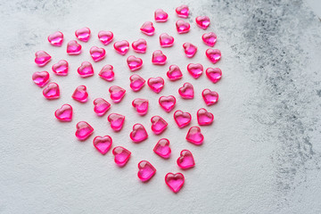 Heart made of pink plastic hearts on a white background
