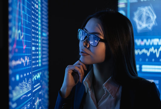 The business woman looks on a large blue screen with chart