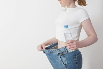 girl with water in bottle pulling her big jeans and showing weight loss