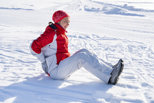 Young Woman Slips And Falls Down On Snowy Road