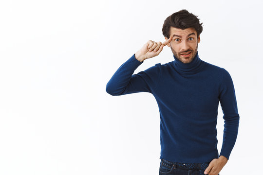 Annoyed, bothered good-looking bearded man in high neck sweater, roll finger over temple and stare camera with disdain, express scorn as someone being stupid or acting crazy, white background