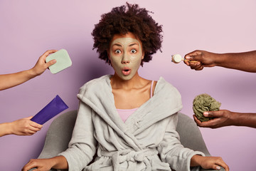 Young surprised woman takes care of her skin, cleans pores with facial mud mask, wears domestic bathrobe, looks with omg expression, sits at armchair against purple background, gets beauty treatments Wall mural
