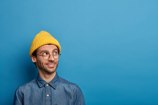 Handsome millennial boy looks aside with glad expression, wears yellow hat and denim shirt, has interesting idea or desire, isolated on blue wall with blank space for your promotion, thinks where go