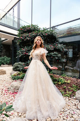 beautiful young bride with blond hair in luxurious wedding dress posing in beautiul patio with...