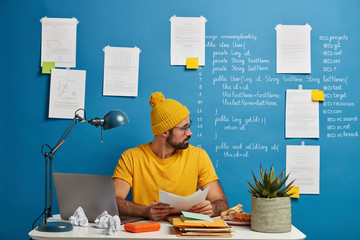 Inexperienced European man looks through paper documents, analyzes during working process, wears yellow hat and t shirt, sits at desktop against blue background with papers and written information