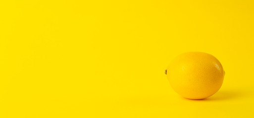 Summer and vitamins background banner. Lemon on a yellow background, minimal food concept