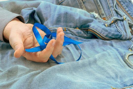 dark blue awareness ribbon in the palm of your hand on blue denim with copyspace