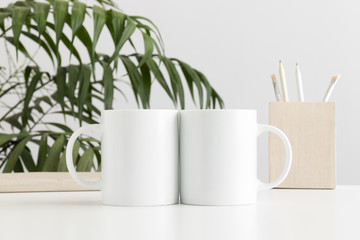 Two mugs mockup with workspace accessories on a white table and a palm plant.
