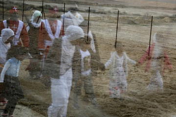 Pilgrims are reflected in a car window as they march towards the Jordan River to participate in a baptism ceremony, near Jericho in the Israeli-occupied West Bank