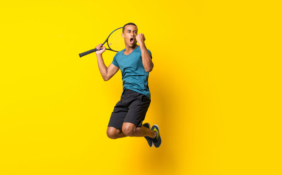 Afro American tennis player man over isolated yellow background