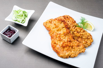 Traditionelles frittiertes Wiener Schnitzel von der Oberschale vom Kalb mit Gurken Salat und Preiselbeeren Marmelade angeboten als closeup auf einem Modern Design Teller