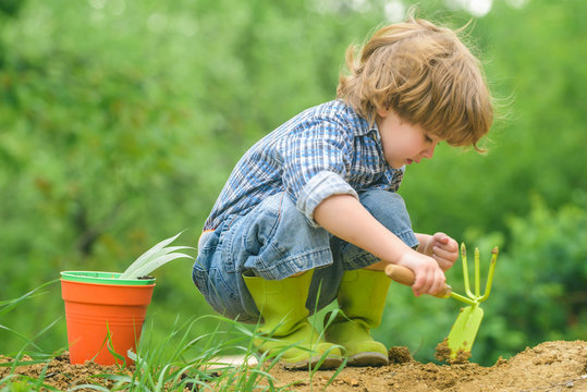 Organic farming. The child works with the ground. The game of the farmer. The boy in the garden.
