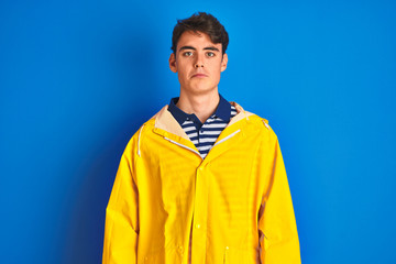 Teenager fisherman boy wearing yellow raincoat over isolated background depressed and worry for distress, crying angry and afraid. Sad expression.