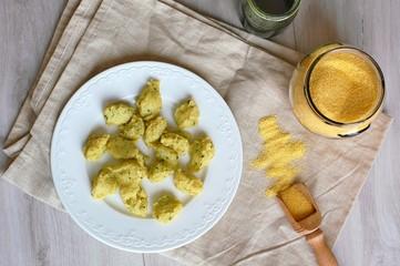 Wall Mural - Corn flour polenta gnocchi with green peste on white plate