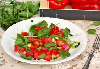 Wall Mural - Vegetable salad with spinach,tomato,pepper,chickpea and greeen pesto on white plate