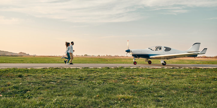 Distant view of stylish young couple holding hands and running on small airplane