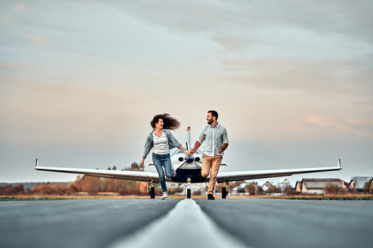 Beautiful romantic couple is holding hands, looking at each other and smiling while running on take-off ground near the aircraft