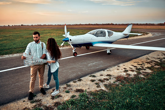 Beautiful romantic couple is standing near private plane in airport.