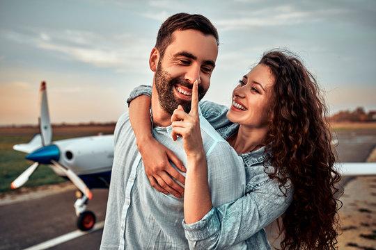Couple in love having fun near private plane