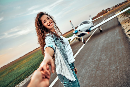 Follow me. Pretty young woman holding hand and leading her friend on summer vacation on a private plane
