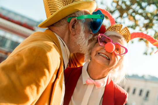 Husband in funny costume kissing his wife