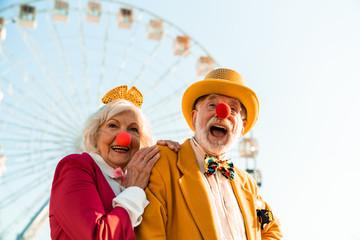 Cheerful mature couple having fun while walking in an amusement park