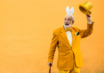 Happy old male wearing playful hat and bunny hairband