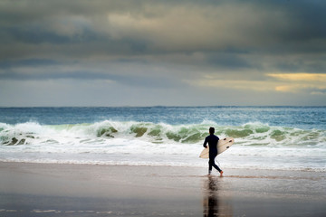 A surfer entering the sea at the Carcavelos Beach in Oeiras, Portugal