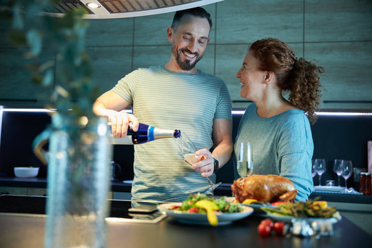 Happy couple having supper in kitchen stock photo