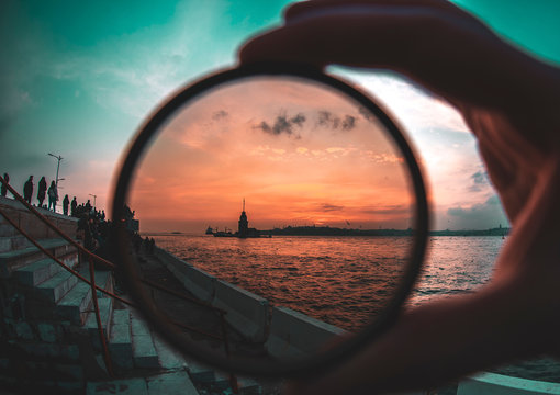 a man holding a photo filter with backgorund of Maiden Tower during sunset