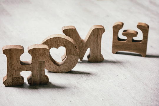 Wooden decorative letters word HOME standing and lying on grey texture table. Concept of love or loss home