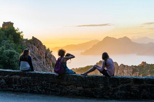 France. Corse. Corsica. Calanques de Piana. Au coucher de soleil, trois touristes admirent le panorama devant elles. : la mer Méditerranée et les rochers. At sunset, three tourists admire the panorama
