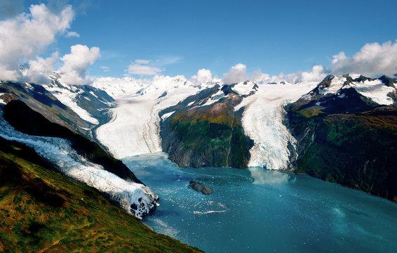 Aerial shot of three majestic glaciers calving into the beautiful azure blue waters of Prince William Sound, Kenai Peninsula. Icebergs float in the water below - Alaska