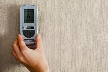 hand with air conditioner remote control