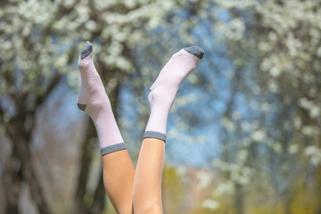 Funny womans legs — Stock Photo  Funny woman legs in pink socks over cherry tree and sky background. Conceptual freedom, travel and holidays image with copy space