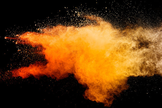 Abstract orange powder explosion isolated on black background.