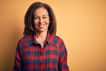 Middle age beautiful woman wearing casual shirt standing over isolated yellow background with a happy and cool smile on face. Lucky person.