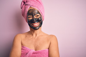 Wall Mural - Middle age brunette woman wearing beauty black face mask over isolated pink background happy face smiling with crossed arms looking at the camera. Positive person.
