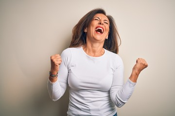Wall Mural - Middle age beautiful woman wearing casual t-shirt standing over isolated white background very happy and excited doing winner gesture with arms raised, smiling and screaming for success. Celebration