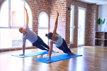 Middle age beautiful sporty couple smiling happy. Practicing yoga doing side plank pose at gym