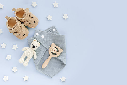 Set of baby shoes, toys and accessories on blue background. Fashion newborn stuff. Flat lay, top view