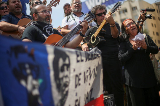 Men play guitars as a woman gestures during an anti-government protest at Plaza Italia, now known as Plaza de la Dignidad (Dignity Square), in Santiago