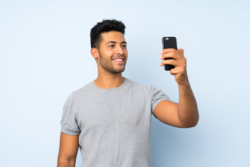Young handsome man over isolated background taking a selfie with the mobile