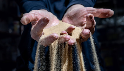 Fine sand trickles through a woman's hands. The sand symbolizes the passing of time.